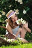 Νέο κορίτσι που καλλιεργεί μεταξύ των άσπρων τριαντάφυλλων Στοκ Εικόνες