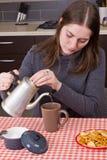 Νέο κορίτσι που κατασκευάζει το τσάι στην κουζίνα Στοκ Φωτογραφία