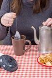 Νέο κορίτσι που κατασκευάζει το τσάι στην κουζίνα Στοκ εικόνα με δικαίωμα ελεύθερης χρήσης