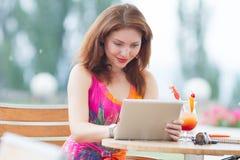 Νέο κορίτσι που κοιτάζει βιαστικά το καθιερώνον τη μόδα PC ταμπλετών Στοκ Εικόνες