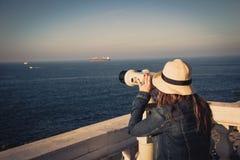 Νέο κορίτσι που κοιτάζει μέσω των ένα χρησιμοποιημένων νόμισμα διοπτρών στη θάλασσα Στοκ φωτογραφία με δικαίωμα ελεύθερης χρήσης
