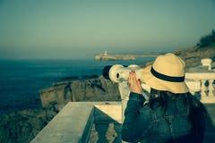 Νέο κορίτσι που κοιτάζει μέσω των ένα χρησιμοποιημένων νόμισμα διοπτρών στη θάλασσα Στοκ εικόνες με δικαίωμα ελεύθερης χρήσης