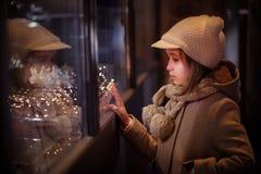 Νέο κορίτσι που κοιτάζει στα παράθυρα που ψωνίζουν, με τη φωτισμένη γιρλάντα Χριστουγέννων στοκ εικόνα