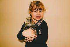 Νέο κορίτσι που κρατά ένα βάζο γυαλιού της καραμέλας στοκ φωτογραφίες