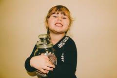 Νέο κορίτσι που κρατά ένα βάζο γυαλιού της καραμέλας στοκ εικόνα με δικαίωμα ελεύθερης χρήσης