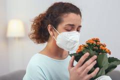 Νέο κορίτσι που κρατά ένα λουλούδι που προκαλεί την αλλεργία της Στοκ Εικόνες