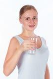Νέο κορίτσι που κρατά ένα ποτήρι του νερού Στοκ Φωτογραφία
