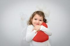 Νέο κορίτσι που κρατά μια κόκκινη καρδιά βελούδου Στοκ φωτογραφία με δικαίωμα ελεύθερης χρήσης