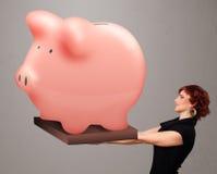 Νέο κορίτσι που κρατά μια τεράστια piggy τράπεζα αποταμίευσης Στοκ εικόνα με δικαίωμα ελεύθερης χρήσης