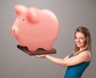 Νέο κορίτσι που κρατά μια τεράστια piggy τράπεζα αποταμίευσης Στοκ Εικόνες