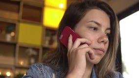 Νέο κορίτσι που μιλά σε ένα τηλέφωνο κυττάρων απόθεμα βίντεο
