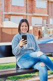 Νέο κορίτσι που μιλά στα μηνύματα smartphone και δακτυλογράφησης με το smartphone στοκ φωτογραφίες