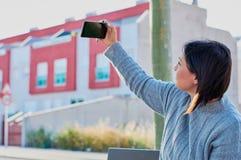 Νέο κορίτσι που μιλά στα μηνύματα smartphone και δακτυλογράφησης με το smartphone στοκ φωτογραφίες με δικαίωμα ελεύθερης χρήσης