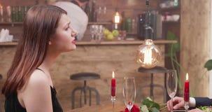 Νέο κορίτσι που μιλά στην ημερομηνία της κατά τη διάρκεια ενός ρομαντικού γεύματος απόθεμα βίντεο