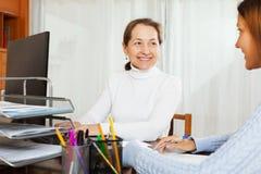 Νέο κορίτσι που μιλά στον υπάλληλο με τον υπολογιστή στοκ εικόνα με δικαίωμα ελεύθερης χρήσης