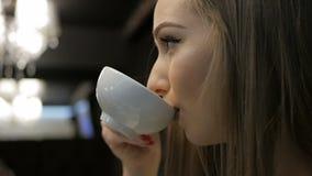 Νέο κορίτσι που πίνει ένα φλυτζάνι του τσαγιού στο εστιατόριο απόθεμα βίντεο