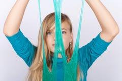 Νέο κορίτσι που παίζει με slime την εκμετάλλευση το μπροστά από το πρόσωπό της στοκ φωτογραφία με δικαίωμα ελεύθερης χρήσης