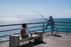 Νέο κορίτσι που παίρνει μια εικόνα ενός ψαρά που αλιεύει μακριά του τέλους της αποβάθρας Χάντινγκτον Μπιτς στοκ φωτογραφίες με δικαίωμα ελεύθερης χρήσης