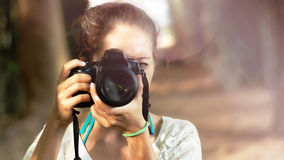 Νέο κορίτσι που παίρνει μια φωτογραφία που κοιτάζει στη κάμερα dslr Στοκ Εικόνες