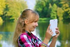 Νέο κορίτσι που παίρνει τη φωτογραφία της λίμνης από το PC ταμπλετών Στοκ φωτογραφία με δικαίωμα ελεύθερης χρήσης