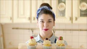 Νέο κορίτσι που παρουσιάζει τα κέικ απόθεμα βίντεο