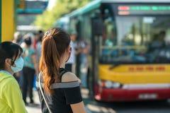 Νέο κορίτσι που περιμένει το λεωφορείο στη στάση λεωφορείου closeup Στοκ Εικόνες