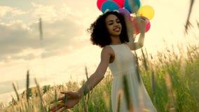 Νέο κορίτσι που περπατά μέσω ενός τομέα σίτου με τα μπαλόνια χρώματος κατά τη διάρκεια του ηλιοβασιλέματος φιλμ μικρού μήκους