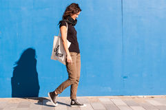 Νέο κορίτσι που περπατά στην οδό με τον μπλε τοίχο στο υπόβαθρο Στοκ Εικόνες