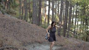 Νέο κορίτσι που περπατά στο δάσος, που ψάχνει ένα δίκτυο στο κινητό τηλέφωνο απόθεμα βίντεο