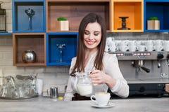 Νέο κορίτσι που προετοιμάζει τον καφέ σε ένα barista καφέδων Στοκ Φωτογραφίες