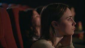 Νέο κορίτσι που προσέχει σκεπτικά την ταινία στον κινηματογράφο Όμορφο πρόσωπο γυναικών στον κινηματογράφο απόθεμα βίντεο