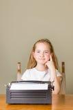 Νέο κορίτσι που σκέφτεται εργαζόμενο στην παλαιά γραφομηχανή Στοκ φωτογραφία με δικαίωμα ελεύθερης χρήσης
