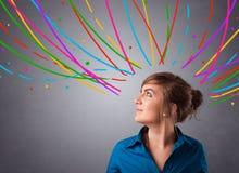 Νέο κορίτσι που σκέφτεται με τις ζωηρόχρωμες αφηρημένες γραμμές εναέριες Στοκ Εικόνα