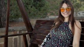 Νέο κορίτσι που ταλαντεύεται σε μια μεγάλη όμορφη ξύλινη ταλάντευση απόθεμα βίντεο