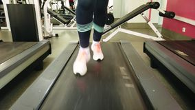 Νέο κορίτσι που τρέχει treadmill στην αθλητική γυμναστική στοκ εικόνες
