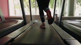 Νέο κορίτσι που τρέχει treadmill στην αθλητική γυμναστική απόθεμα βίντεο