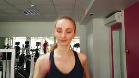 Νέο κορίτσι που τρέχει treadmill στην αθλητική γυμναστική φιλμ μικρού μήκους