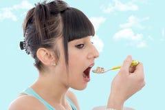 Νέο κορίτσι που τρώει τα δημητριακά προγευμάτων Στοκ Εικόνες