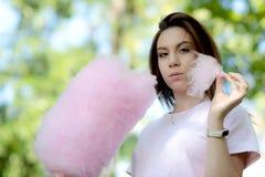 Νέο κορίτσι που τρώει την καραμέλα βαμβακιού στο πάρκο στοκ εικόνα