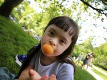 Νέο κορίτσι που τρώει το βερίκοκο στο πάρκο Στοκ Φωτογραφία