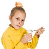 Νέο κορίτσι που τρώει το γιαούρτι Στοκ Φωτογραφίες