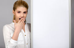 Νέο κορίτσι που φαίνεται έκπληκτη στάση κοντά σε έναν λευκό πίνακα. Στοκ φωτογραφίες με δικαίωμα ελεύθερης χρήσης