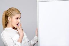 Νέο κορίτσι που φαίνεται έκπληκτη στάση κοντά σε έναν λευκό πίνακα. Στοκ Φωτογραφίες