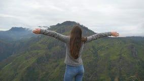 Νέο κορίτσι που φθάνει επάνω στην κορυφή του βουνού και των αυξημένων χεριών Τουρίστας γυναικών που στέκεται στην άκρη του όμορφο απόθεμα βίντεο