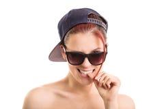 Νέο κορίτσι που φορά τα γυαλιά ηλίου και ένα αθλητικό καπέλο στοκ φωτογραφία