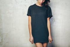 Νέο κορίτσι που φορά την κενή μαύρη μπλούζα συγκεκριμένος ελαφρύς μέσος τοίχος σημείων ανασκόπησης οριζόντιος στοκ εικόνες