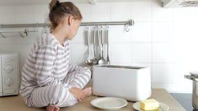 Νέο κορίτσι που φορά τις πυτζάμες που βάζουν το ψωμί στη φρυγανιέρα φιλμ μικρού μήκους