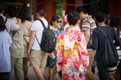 Νέο κορίτσι που φορά το ιαπωνικό κιμονό που στέκεται μπροστά από το ναό Sensoji στο Τόκιο, Ιαπωνία Το κιμονό είναι ένα ιαπωνικό π Στοκ Εικόνες