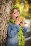 Νέο κορίτσι που φορούν το πράσινο μαντίλι και καπέλο που τρώει τη Apple έξω Στοκ Εικόνες