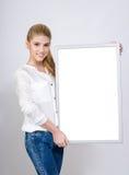 Νέο κορίτσι που χαμογελά και που κρατά έναν λευκό κενό πίνακα. Στοκ Φωτογραφίες